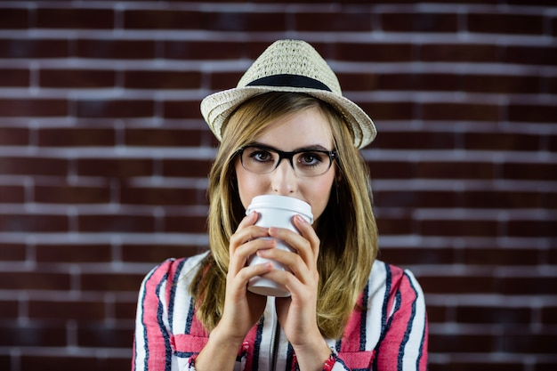 Woman drinking a beverage and wearing a hat