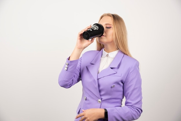 Woman drinking black cup of coffee on white