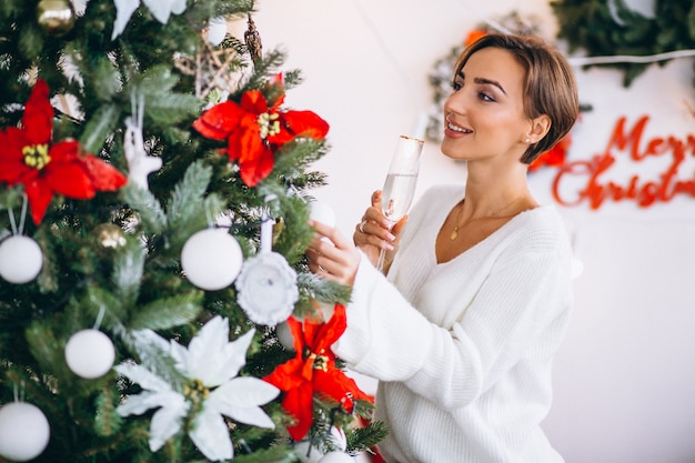 Woman drinking champaigne by christmas tree