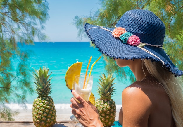 Woman drinking cocktail in the beach bar