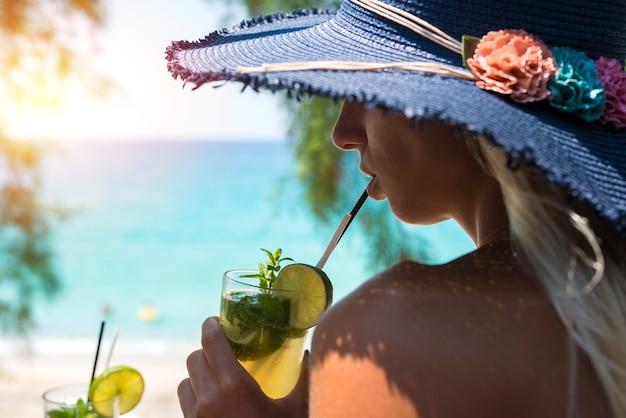 Donna che beve cocktail al bar della spiaggia