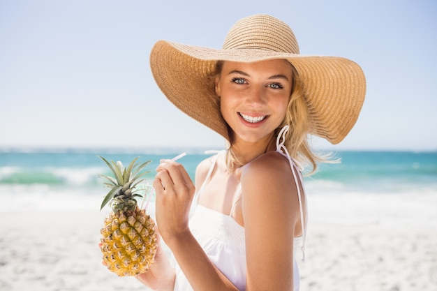 Woman drinking cocktail in pineapple
