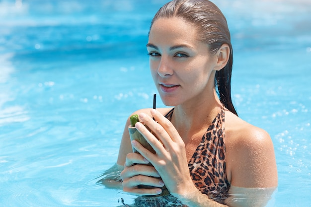 Woman drinking cocktail with straw with flirting and dreaming facial expression wearing swimsuit with leopard print.