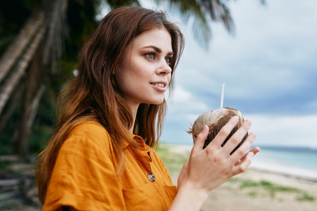 A woman drinking coconut water in the beach with palm trees