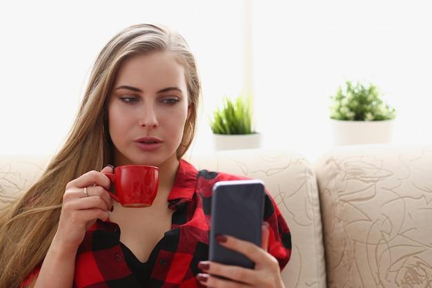 Женщина пьет кофе и смотрит на ноутбук