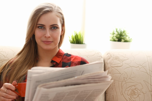 ソファに座ってコーヒーを飲み、読書をしている女性