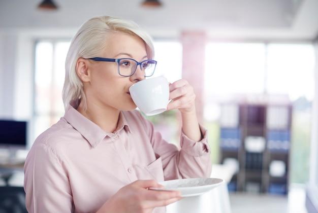 Женщина пьет кофе в офисе