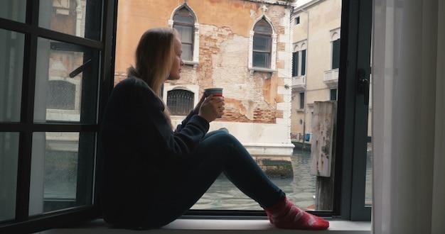 여자가 커피를 마시고 베니스보기를보고