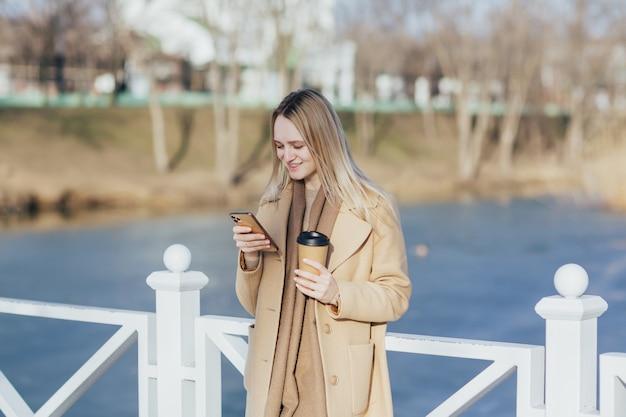 コーヒーを飲み、スマートフォンを使用している女性