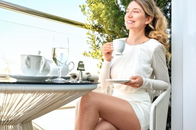 Женщина пьет кофе на террасе и наслаждается видом