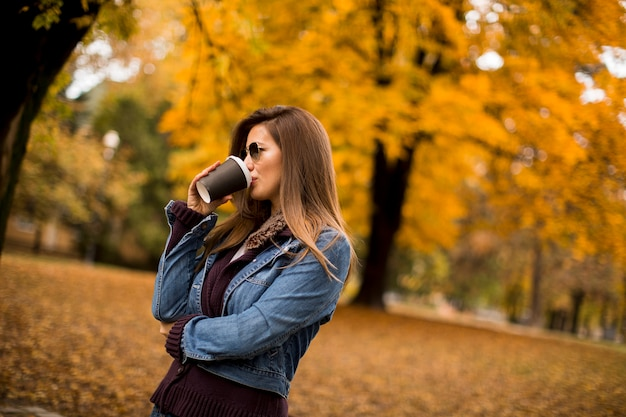 Woman drinking coffee in autumn park