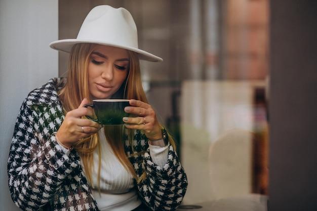Donna che beve il caffè in un bar, seduto dietro il vetro