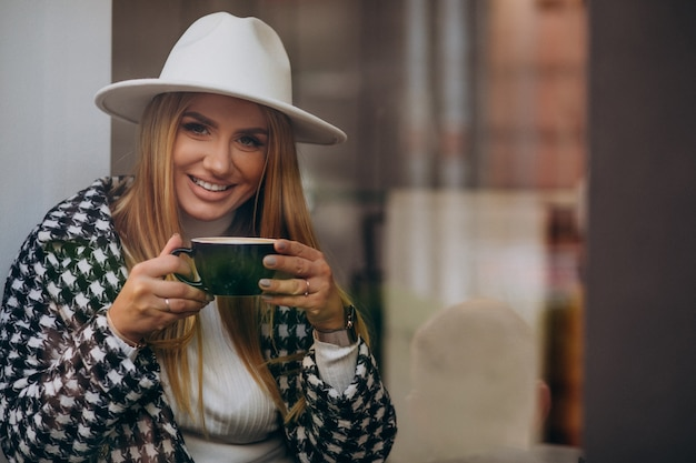 Woman drinking coffee in a cafe, sitting behind the glass