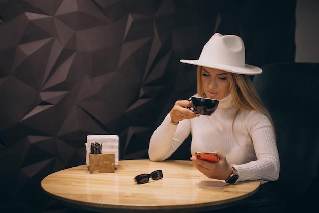 Donna che beve il caffè in un bar e parla al telefono