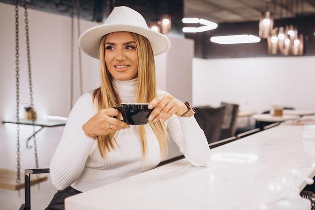 Donna che beve il caffè in un bar