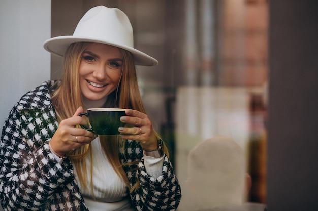 유리 뒤에 앉아 카페에서 커피를 마시는 여자
