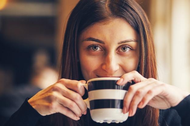 レストランで朝コーヒーを飲む女性