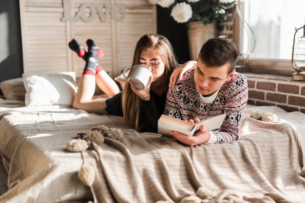 Woman drinking coffee lying with her boyfriend reading book on bed