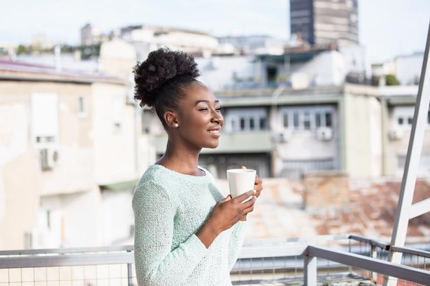 Женщина пьет кофе на балконе