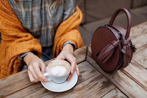 コーヒーを飲む女性。テーブルの上のスタイリッシュなバッグ。グレーのドレスとオレンジのチェック柄を着ています。カフェで居心地の良い朝を楽しんでください。