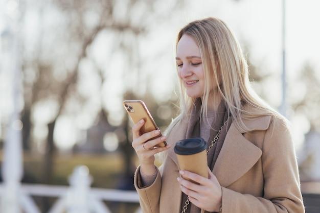 コーヒーのテイクアウトを飲み、スマートフォンを使用している女性