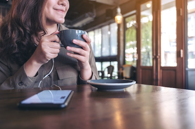 Woman drinking coffee while listening to music with mobile phone and earphone in cafe