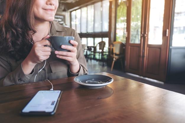 カフェで携帯電話とイヤホンで音楽を聴きながらコーヒーを飲む女性