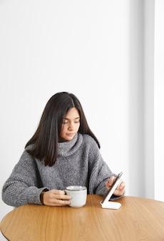 전화를 사용하는 동안 커피를 마시는 여자