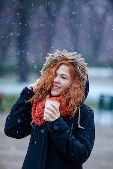 Woman drinking coffee on a winter snowy day