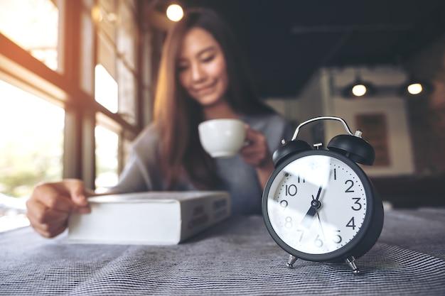 目覚まし時計でコーヒーを飲む女性