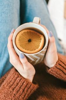 Donna che beve una tazza di tè caldo alle erbe all'arancia