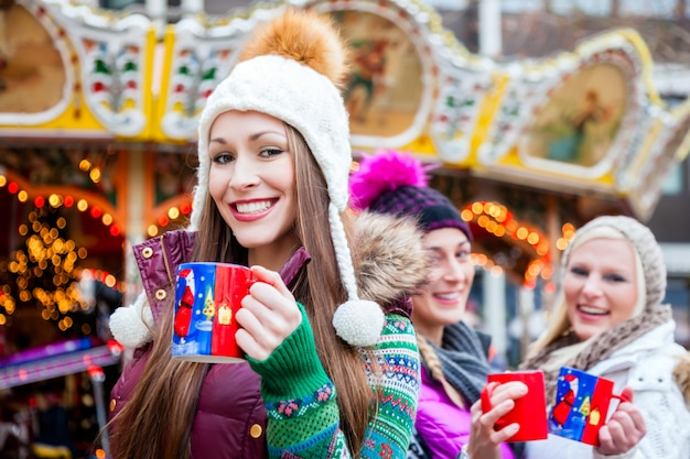 Woman drinking eggnog on german christmas market