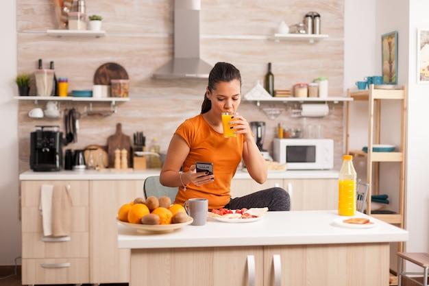 Женщина пьет свежий апельсиновый сок утром во время просмотра на смартфоне на кухне