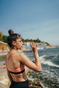 Donna che beve acqua fresca dalla bottiglia dopo l'esercizio sulla spiaggia