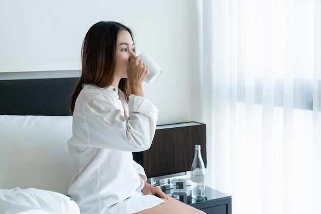 Женщина пьет из чашки, сидя в постели