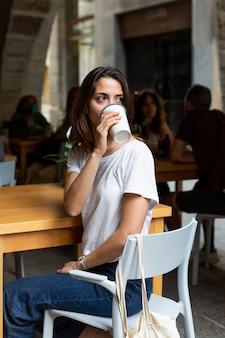 Donna che beve da un destinatario sostenibile