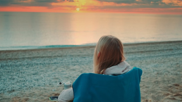 Woman drinking from thermal mug and sitting on the beach before sunrise