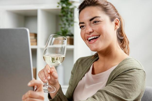 노트북을 사용하는 동안 와인을 마시는 여자