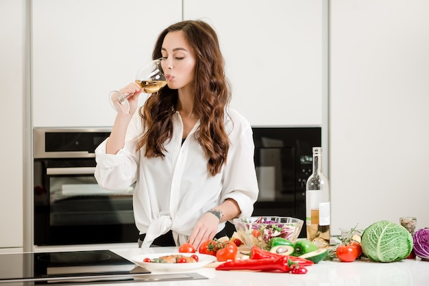 Woman drinking a glass of white wine at the kitchen while cooking salad