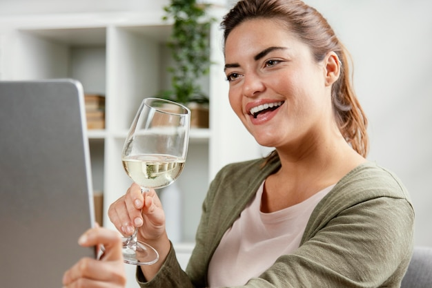 Donna che beve un bicchiere di vino durante l'utilizzo di laptop