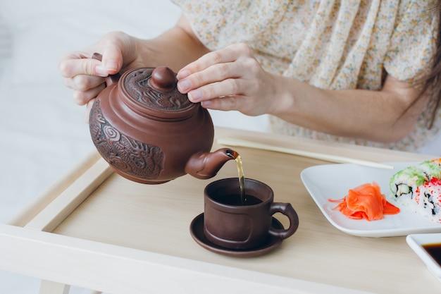 Женщина пьет зеленый чай и ест суши