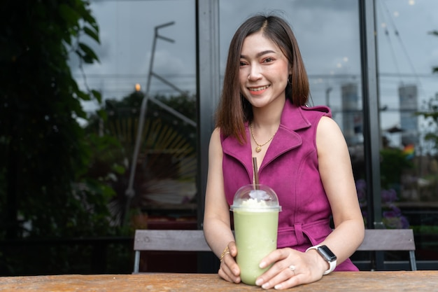 Woman drinking green tea frappe in cafe