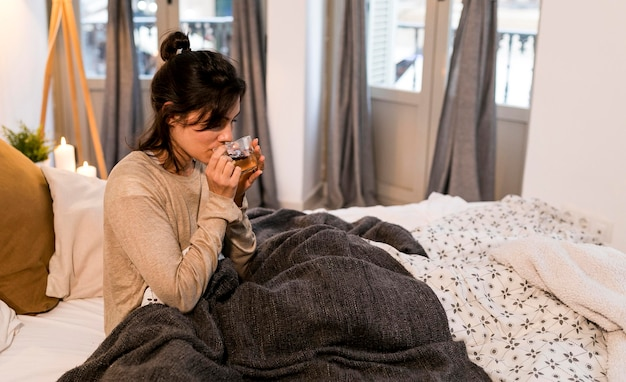 Woman drinking her tea in bed
