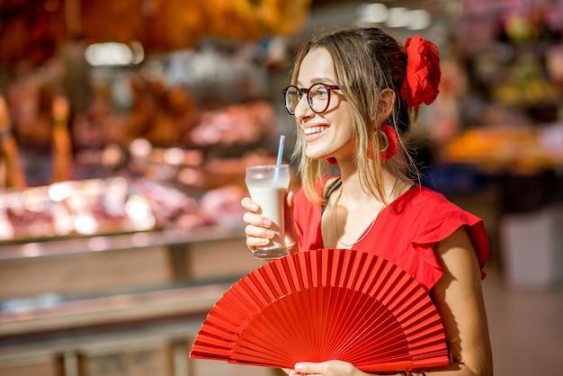 バレンシア市の中央食品市場に立って、アーモンドから作られた伝統的なスペインの飲み物、オルチャータを飲む女性