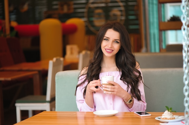 Woman drinking hot cappuccino coffee and eating cake at a cafe.