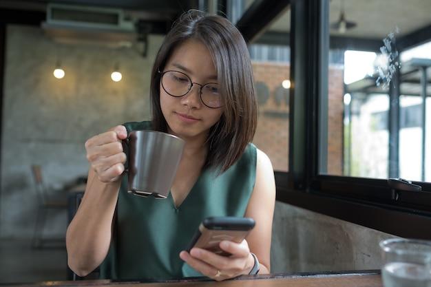 ホットコーヒーを飲み、スマートフォンを再生する女性、リラックス時間、中毒者の電話、ショッピング時間、送信されたメッセージ