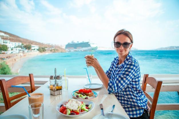 リゾートレストランで海を望む高級ホテルのテラスでホットコーヒーを飲む女性