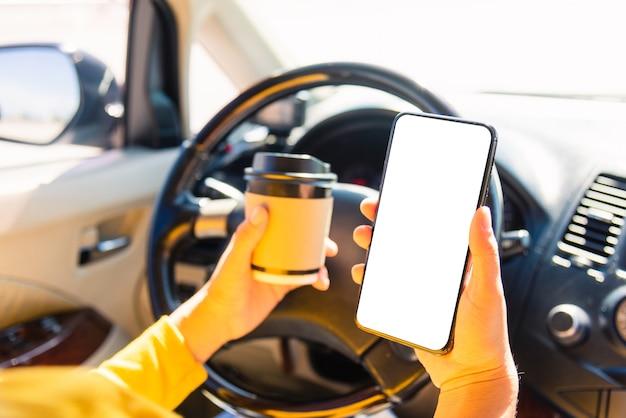차 안에서 뜨거운 커피 테이크 아웃 컵을 마시고 차를 운전하는 동안 스마트 폰 빈 화면을 사용하는 여자
