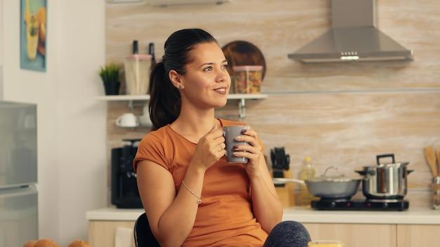 아침에 일어나기 위해 뜨거운 커피를 마시는 여자. 아침에 커피 한 잔을 즐기는 레이디. 행복한 주부는 혼자 건강한 식사를 하며 휴식을 취하고 있다