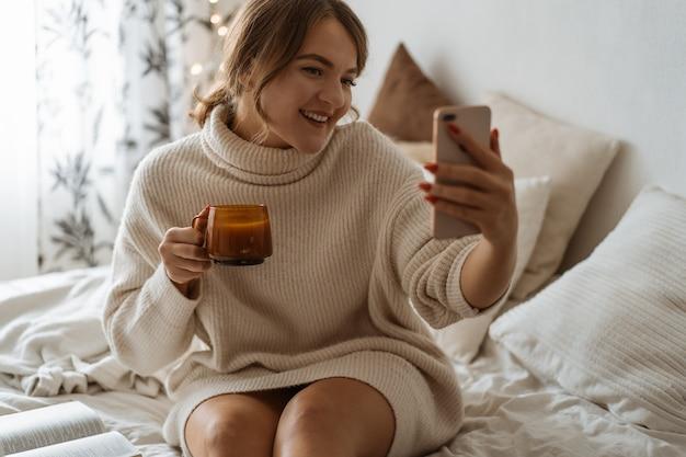 熱いお茶を飲み、自分撮りをする女性。快適なライフスタイル。
